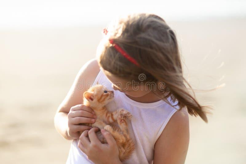 Gato del beb? de la tenencia de la ni?a Ni?os y animales dom?sticos fotografía de archivo libre de regalías