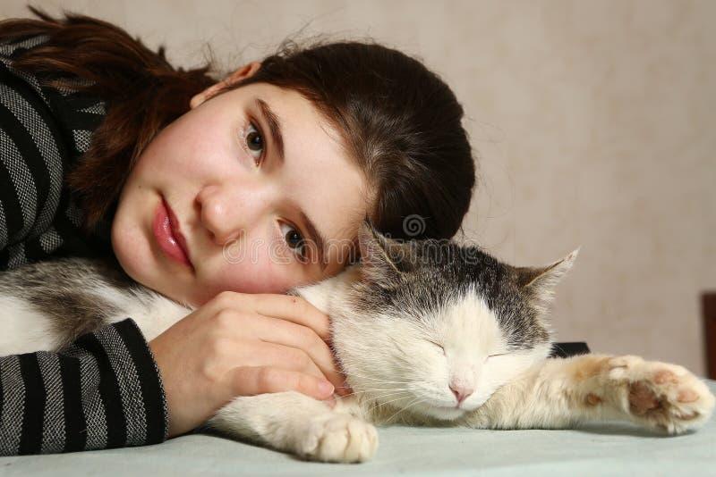 Gato hermoso adolescente del abrazo de la muchacha imagen de archivo