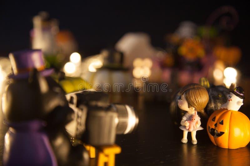 Gato oscuro del mago usando la cámara para tomar la foto de la muchacha con las calabazas y el fantasma delante de la casa del pa imagen de archivo libre de regalías
