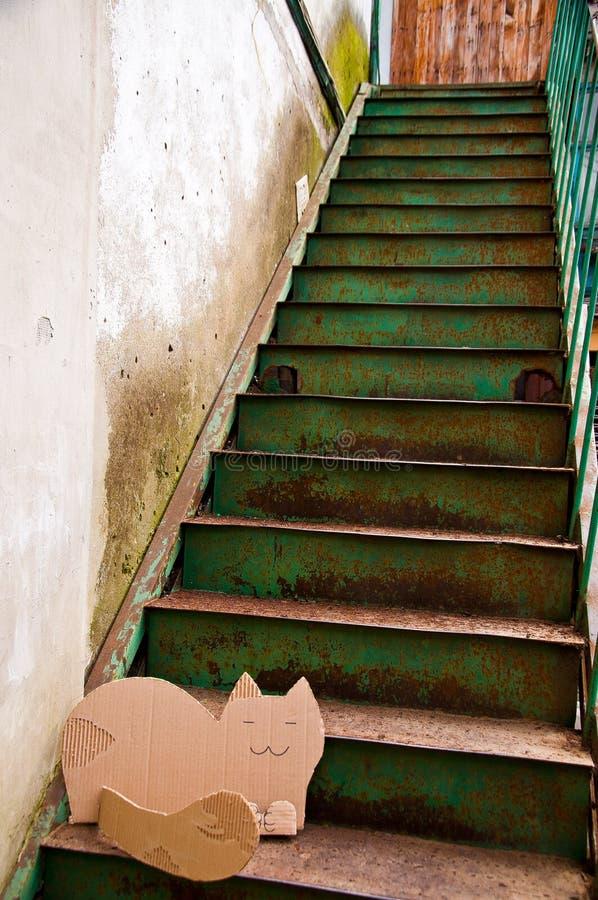 Gato sonriente de la cartulina en las escaleras oxidadas en patio viejo en Odessa Ukraine imagen de archivo libre de regalías