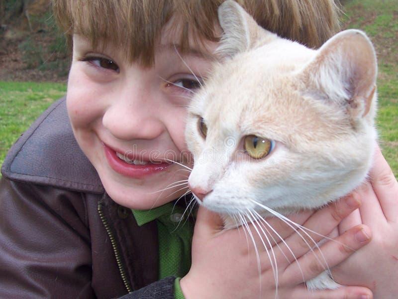 Gato y muchacho de ojos verdes imagenes de archivo