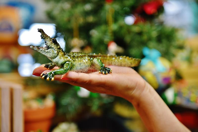 Gator made glass on palm. There is gator made from glass on the palm at the time of celebrating New Year, very dangerous in life , but very cuite on the woman`s royalty free stock photography