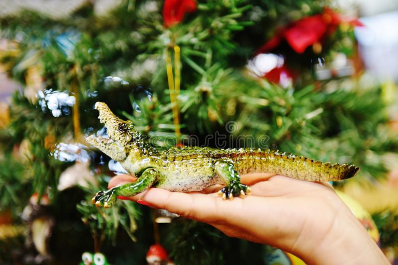 Gator made from glass on palm. There is gator on the palm at the time of celebrating New Year, very dangerous in life , but very cuite on the woman`s palm stock photos