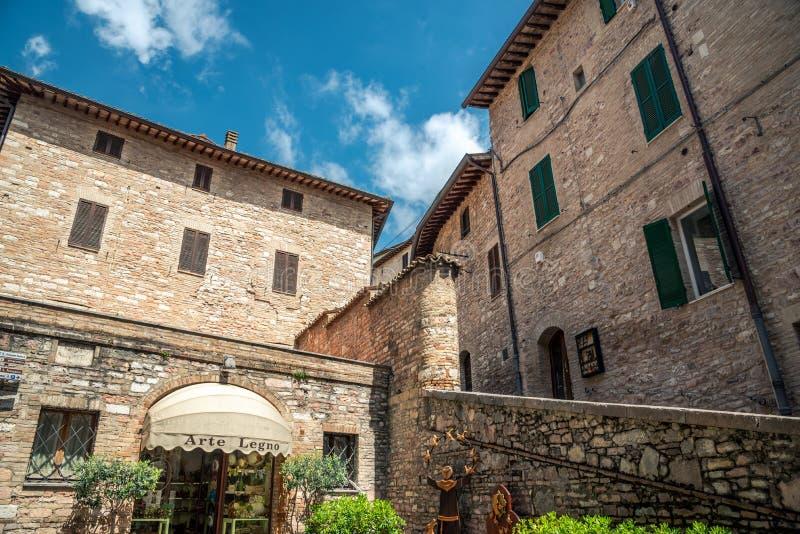 Gator och röda flaggor för härlig byggnadswhit i den medeltida staden av Assisi, Umbria Italy arkivbilder