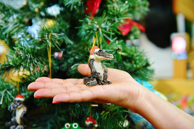 Gator santa claus hat on palm. There is gator in Santa Claus hat on the palm at the time of celebrating New Year, very dangerous in life , but very cuite on the royalty free stock image