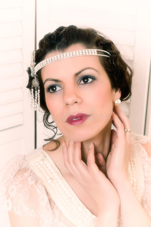 Gatsby style portrait. Closeup of a beautiful vintage 1920 lady with flapper dress and headband stock image