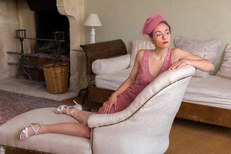 Gatsby woman on chaise longue. Sensual 1920s woman in pink flapper dress sitting on an antique chaisee longue or recliner royalty free stock photography