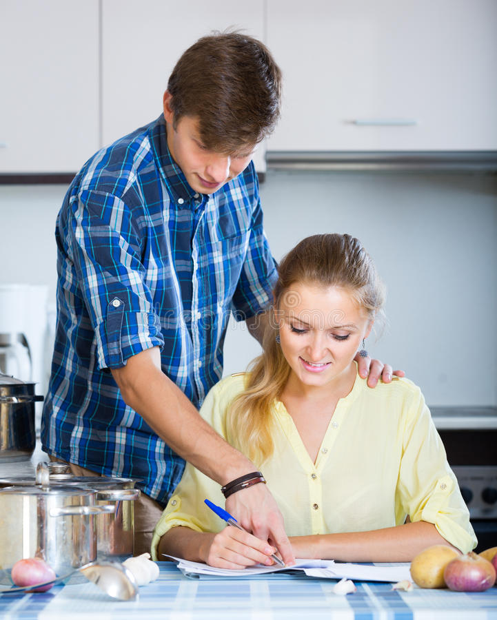 Gatten, die Dokumente unterzeichnen und an der Küche lächeln lizenzfreie stockfotografie