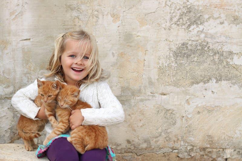 Gattini svegli della holding della ragazza fotografia stock libera da diritti