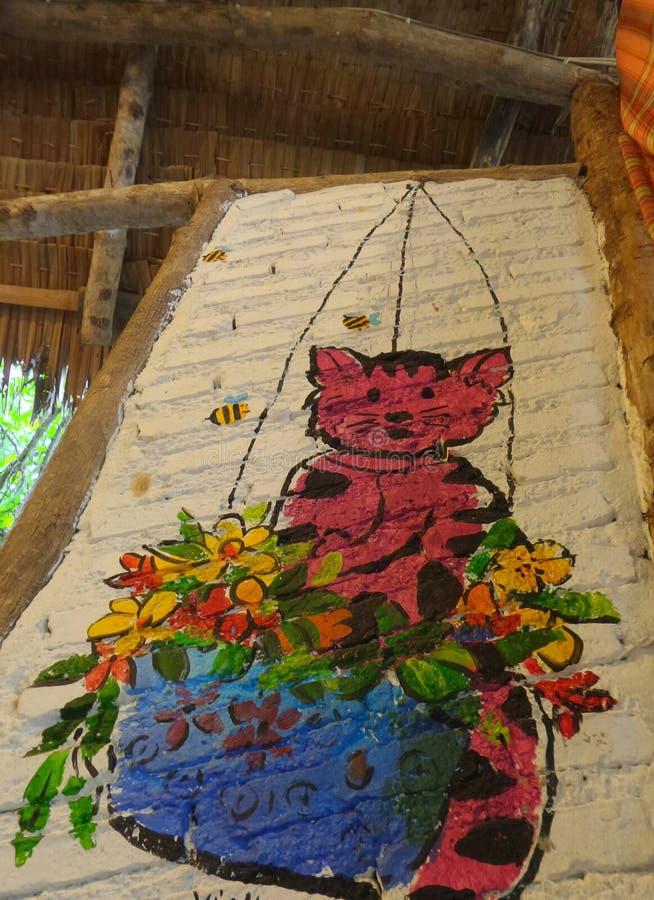 Gattino nella pittura d'attaccatura del canestro del fiore sul muro di mattoni bianco fotografie stock libere da diritti