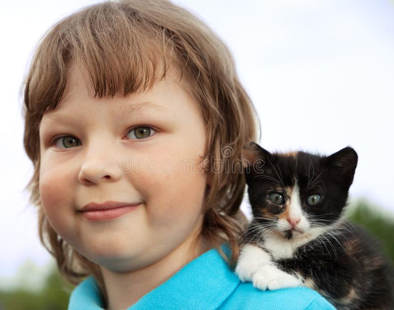 Gattino sul braccio del ragazzo all'aperto, bambino enorme il suo animale domestico di amore immagine stock
