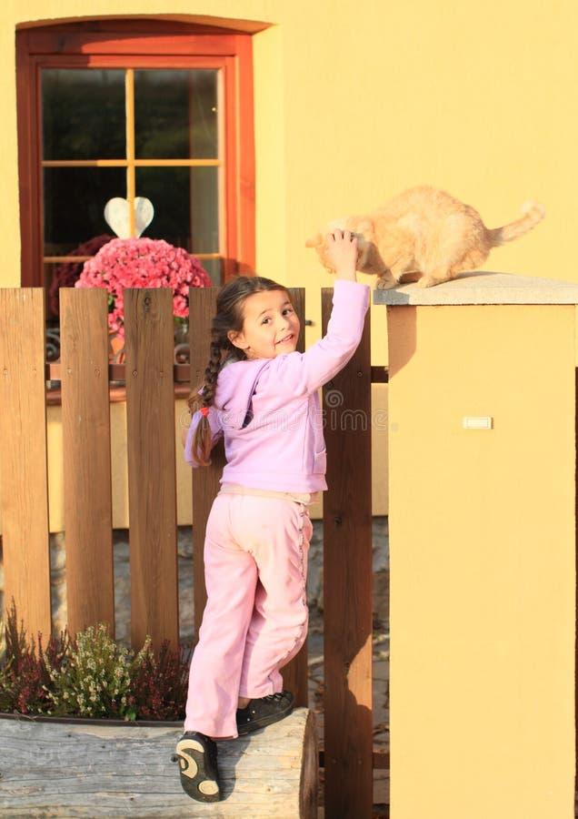 Gatto di carezza della bambina fotografia stock