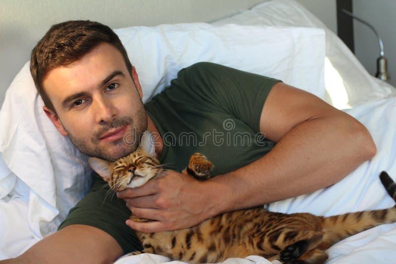 Gatto esotico che dorme con il suo proprietario bello fotografia stock