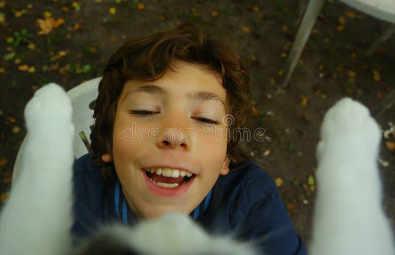 Gatto felice della presa del ragazzo dell'adolescente dalla fine dell'albero su immagine stock