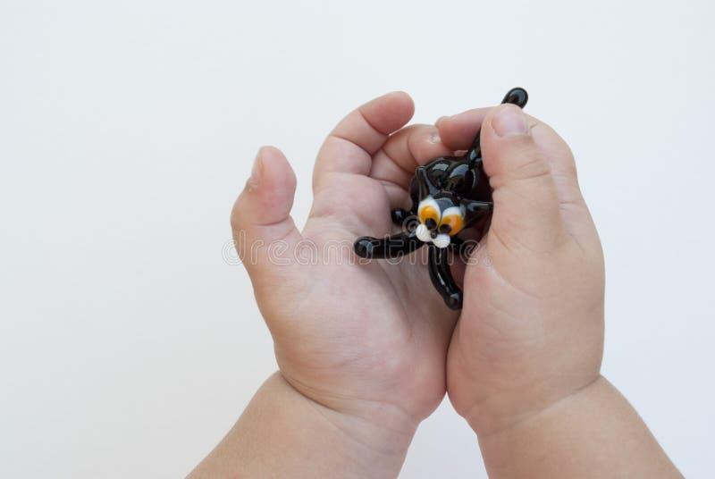 Gatto nero di vetro del giocattolo nelle mani di un bambino piccolo su un fondo bianco Occhi di giallo fotografia stock