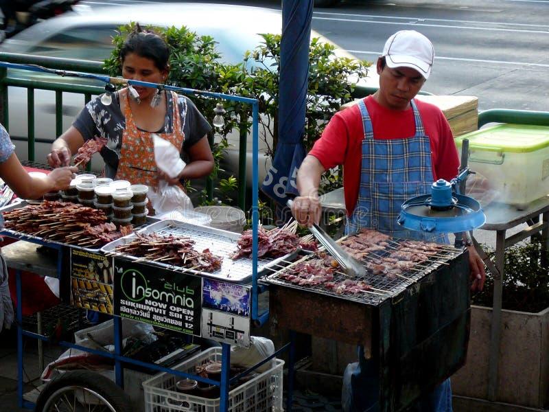 Gatuförsäljare som lagar mat kött på gatorna av Bangkok Thailand royaltyfri fotografi