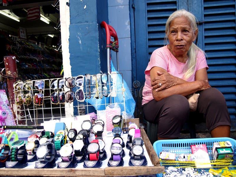 Gatuförsäljaren för den gamla damen säljer klockor och eyewearen royaltyfria bilder