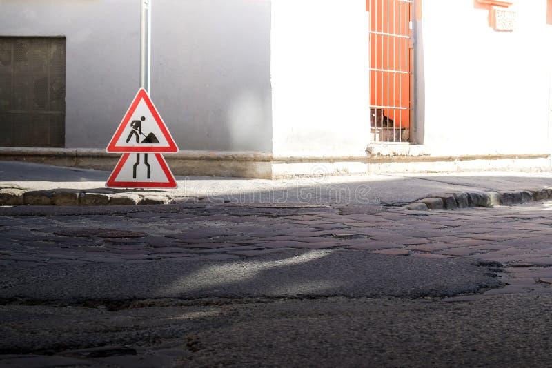 Gatugatan med vägskylt, asfaltlappar och kullsten royaltyfri bild