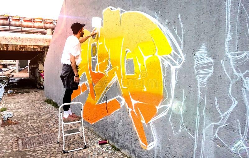 Gatukonstnärer som arbetar med färgat graffiti på den offentliga rymdväggen - Modern konst föreställer sig att man målar levande  arkivfoto