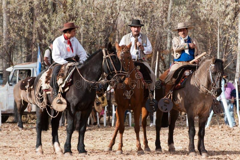 Gauchos que montan un caballo foto de archivo