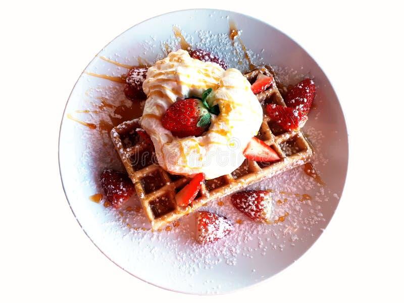 Gaufres avec de la crème et des fraises du plat blanc images libres de droits