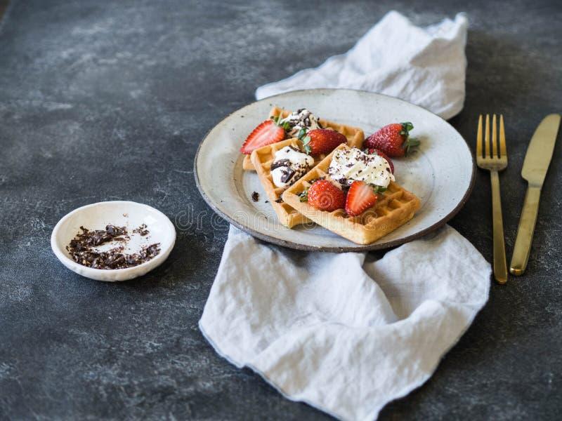Gaufres belges avec de la crème, le chocolat et des fraises de lait d'un plat gris image libre de droits