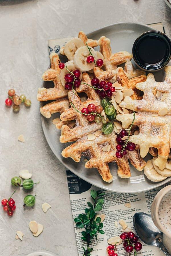 gaufres belges croustillantes aux currants rouges, aux airelles, au sirop d'érable et au sucre en poudre sur la plaque de céramiq image libre de droits