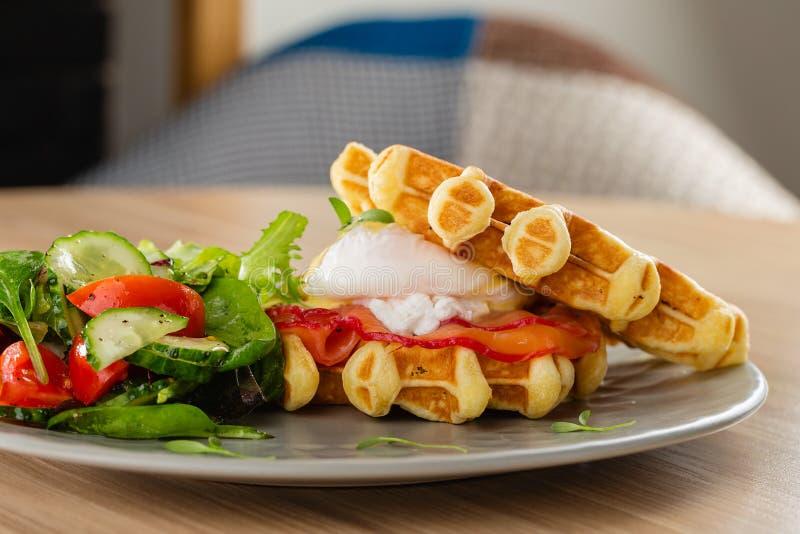 Gaufres belges savoureuses avec l'oeuf poché, les saumons et la salade Oeufs photos stock