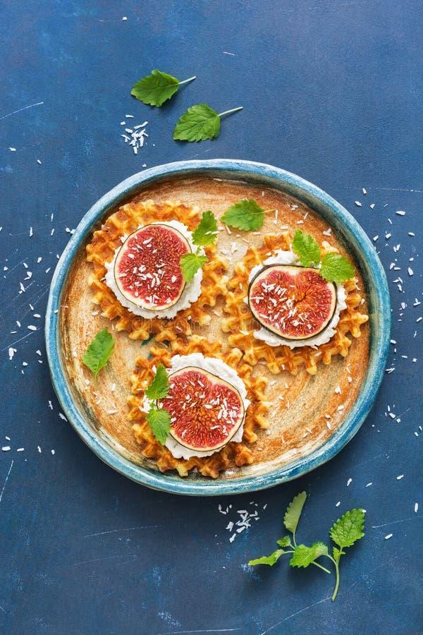 Gaufres croustillantes de petit déjeuner avec de la crème et figues arrosées avec des flocons de noix de coco sur un fond grunge  photographie stock
