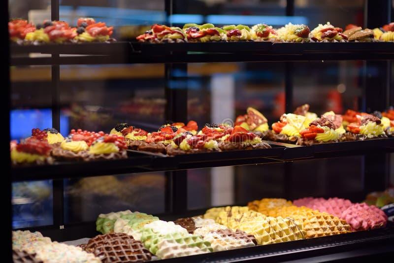 Gaufres de Belge et de Liège avec du chocolat, les baies, la sauce douce, la crème dans la fenêtre d'un café ou le magasin image stock