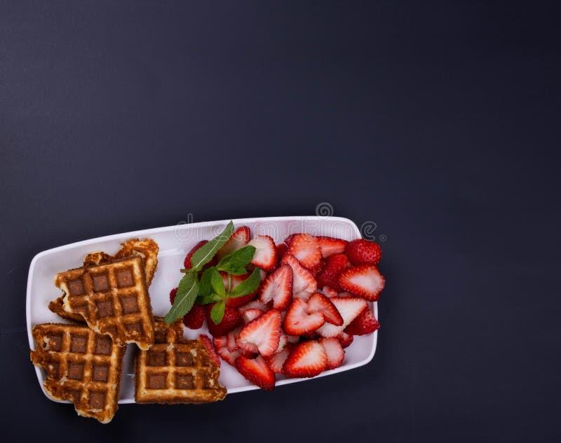 Gaufres libres fraîchement cuites au four de gluten avec des fraises sur la menthe sur un plat rectangulaire photo stock