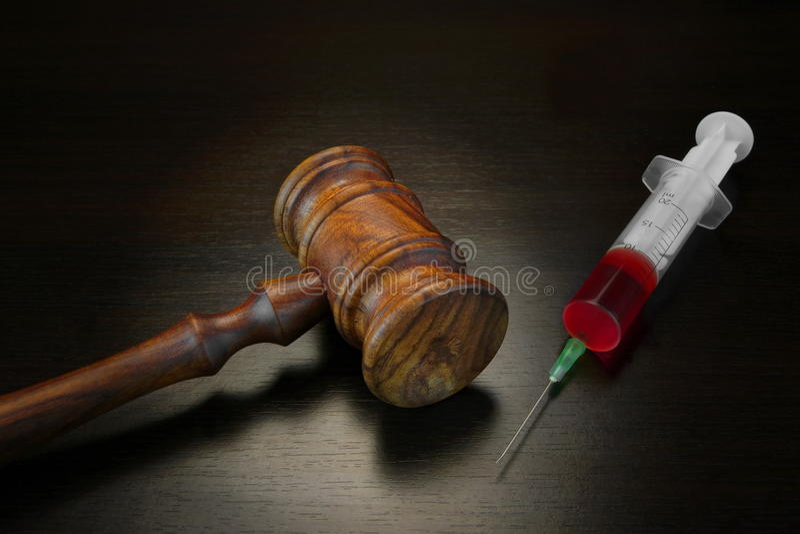 Gavel δικαστών και ιατρική σύριγγα εγχύσεων σε μαύρο ξύλινο Backg στοκ εικόνα