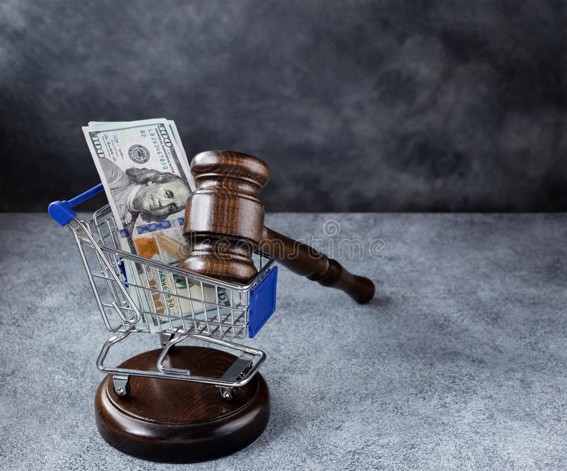 Gavel and dollars in cart. Gavel and dollars in shopping trolley cart on gray background with copy space. Corrupt court cases concept stock photo