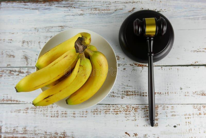 Gavel e casco di banane su fondo di legno Concetto di CAUSA immagine stock libera da diritti