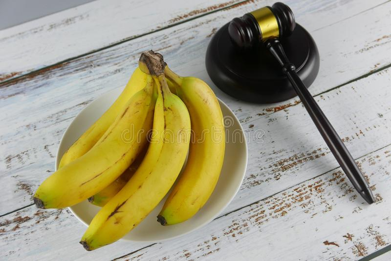 Gavel e casco di banane su fondo di legno Concetto di CAUSA immagini stock libere da diritti