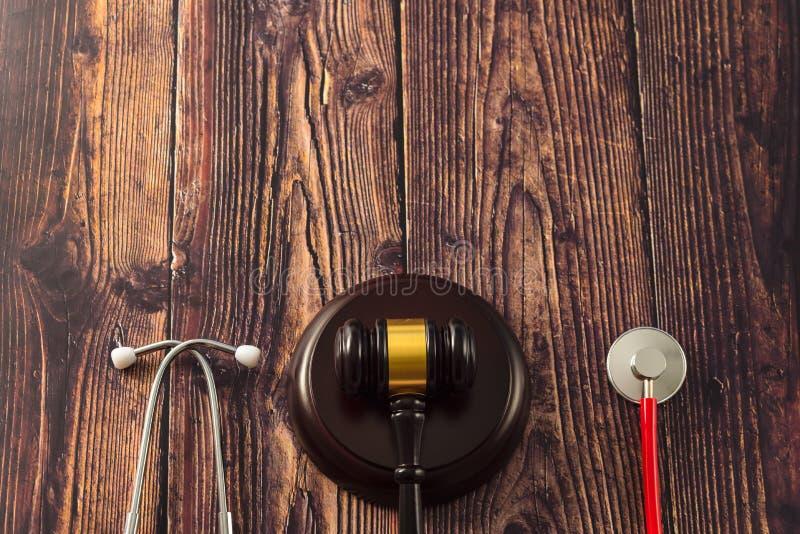 Gavel en stethoscoop op houten achtergrond, donkere omgeving stock afbeelding