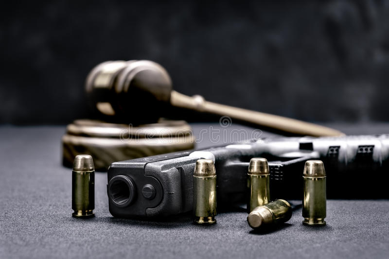 Gavel and gun rights. A handgun with bullets symbolizing gun rights while framed with a judge`s gavel and block royalty free stock image
