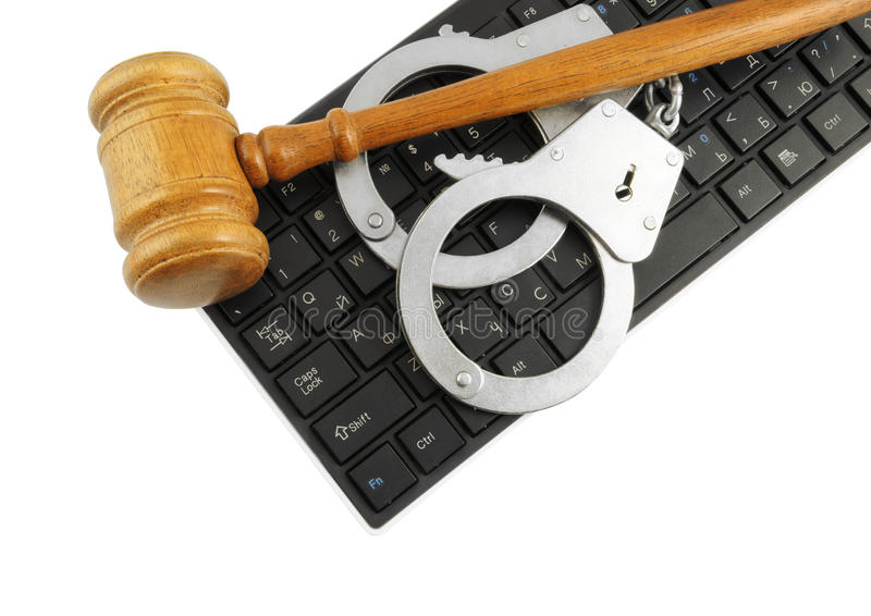 Gavel and handcuffs on computer keyboard. Isolated on white stock image