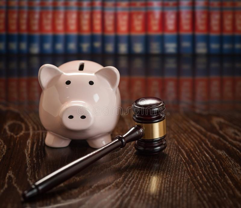 Gavel and Piggy Bank on Table With Law Books In Background stock photography