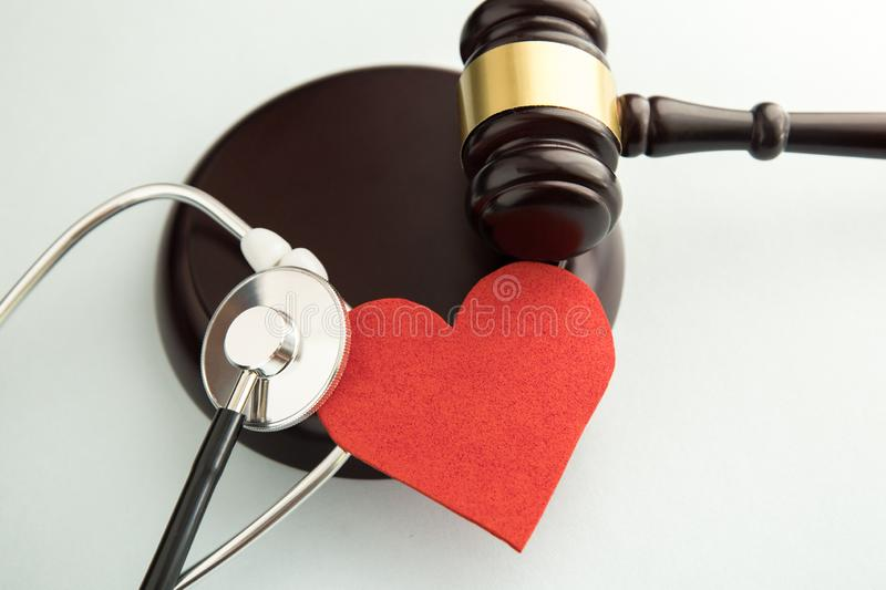 Gavel with red heart and stethoscope on white. Medical stock photography