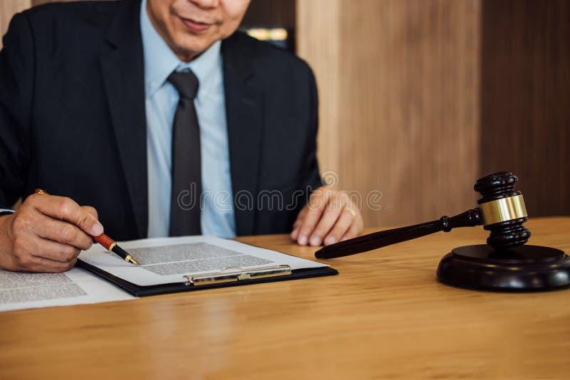 Gavel sulla tavola di legno ed avvocato o giudice che lavorano con l'accordo nel tema dell'aula di tribunale, nel concetto di leg immagine stock libera da diritti