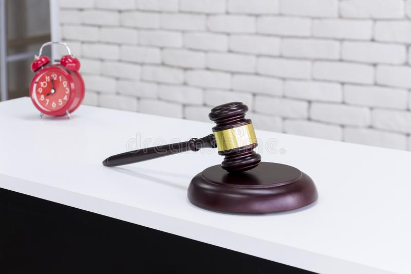 Gavel wood and brass with old alarm clock on white background in auction or law enforcement concept stock image