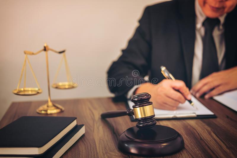 Gavel on wooden table and Lawyer or Judge working with agreement. In Courtroom theme, Justice and Law concept royalty free stock photos