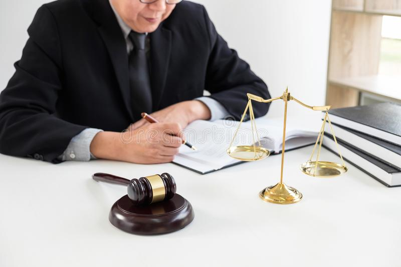 Gavel on wooden table and Lawyer or Judge working with agreement. In Courtroom theme, Justice and Law concept royalty free stock image