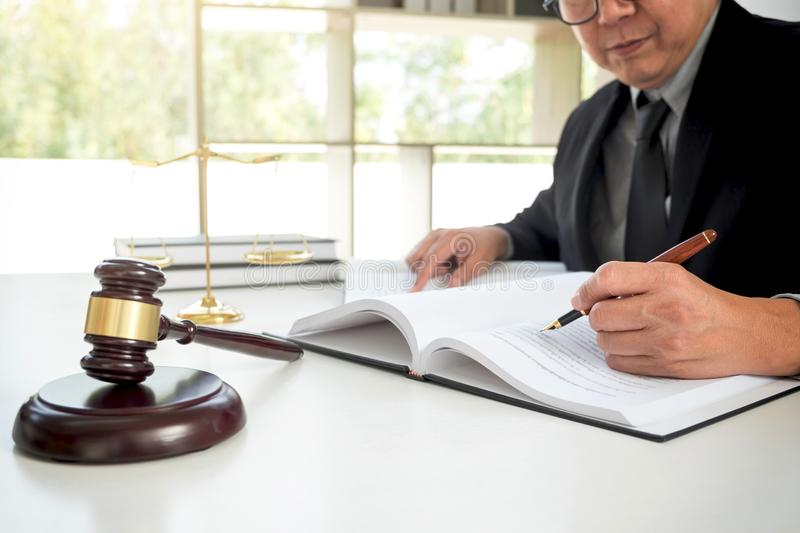 Gavel on wooden table and Lawyer or Judge working with agreement. In Courtroom theme, Justice and Law concept royalty free stock photography