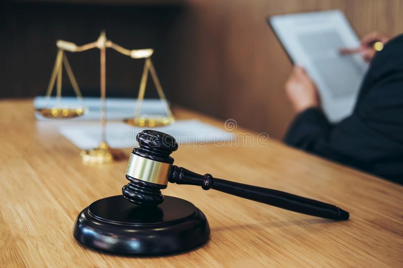 Gavel on wooden table and Lawyer or Judge working with agreement. In Courtroom theme, Justice and Law concept stock photos