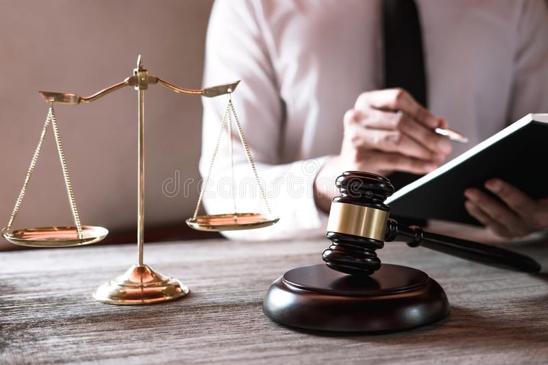 Gavel on wooden table and Lawyer or Judge working with agreement. In Courtroom theme, Justice and Law concept stock image