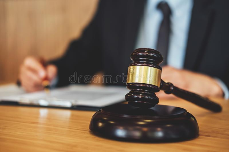Gavel on wooden table and Lawyer or Judge working with agreement. In Courtroom theme, Justice and Law concept royalty free stock photo