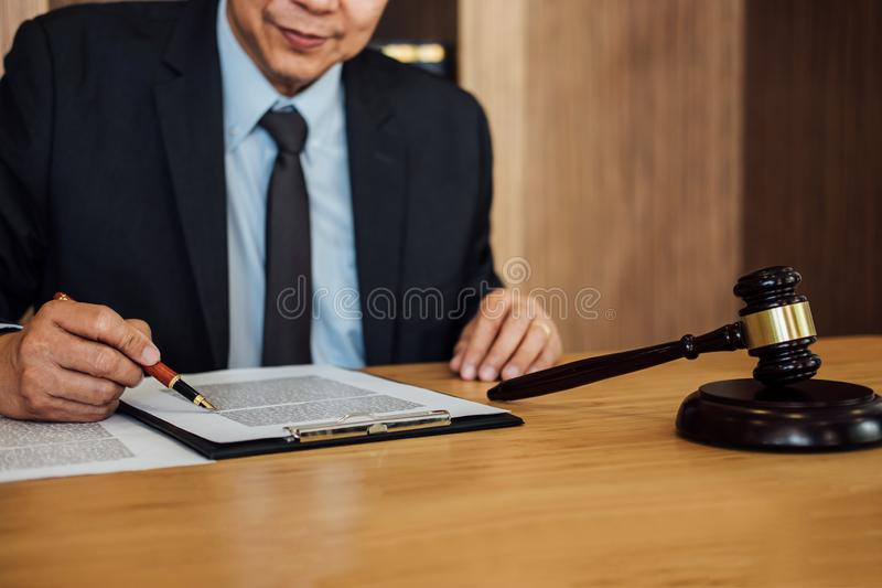 Gavel on wooden table and Lawyer or Judge working with agreement in Courtroom theme, Justice and Law concept royalty free stock image