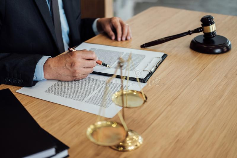 Gavel on wooden table and Lawyer or Judge working with agreement in Courtroom theme, Justice and Law concept.  stock photos